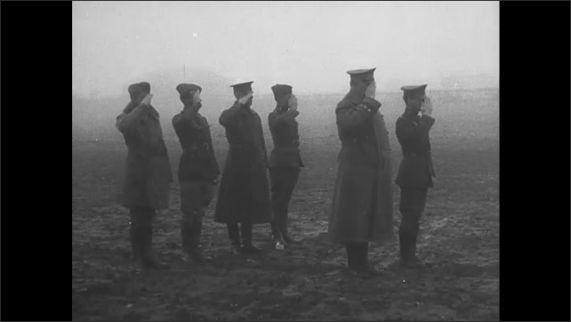 1910s: Soldiers and dog smile and pose on biplane near hangar. General and officers salute on foggy field. Soldiers salute and stand near biplane in fog