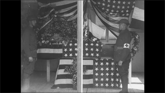 1910s: Soldiers stand at attention near flag-draped coffin in medical tent. Soldiers salute and pay respects to coffin at funeral tent.