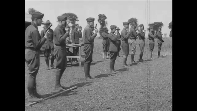 1910s France: Line of soldiers practicing aiming and shooting guns at firing range.