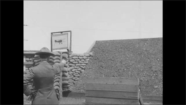 1910s France: Firing range.  Man shoots at printed airplane target as it moves along.  Man shoots at clay pigeons.