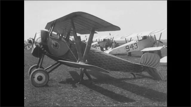 1910s: Soldiers and pilots gather near biplanes in field. Biplane propellers spin on airfield near hangars. Soldier inspects biplane. Biplane takes off on grassy field.