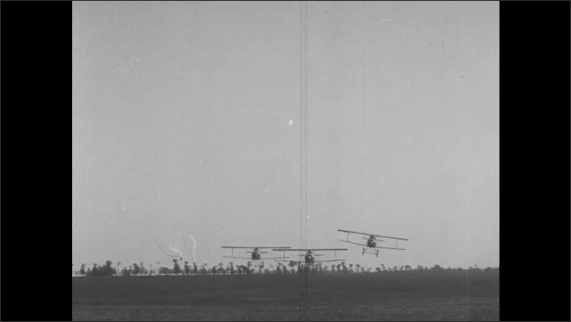 1910s: Biplanes fly low over grassy field.  Pilot and gunner sit in cockpits of biplane.