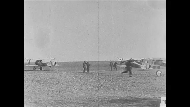 1910s: Biplane takes off from grassy field. Soldiers spin propellers on biplanes in airfield.