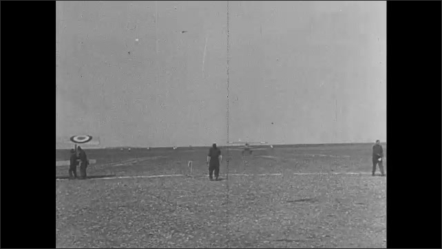 1910s: Biplanes takes off from grassy field. Soldiers walk away from airfield.