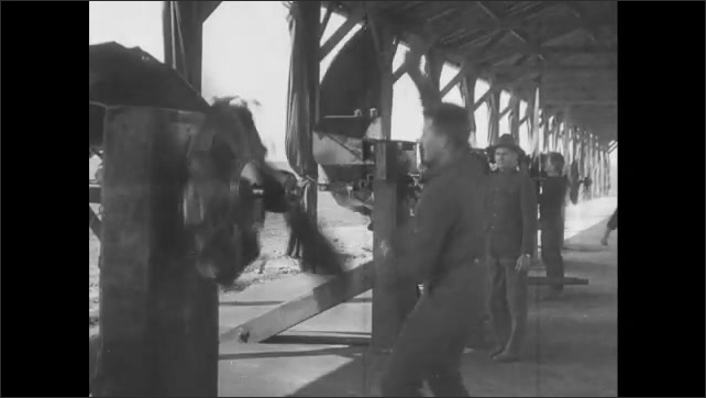 1910s: Men construct biplane engines in factory workshop. Men test propellers and biplane engines in factory hangar.