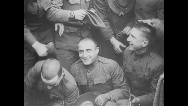 1910s: soldiers crouched with shaved heads, soldiers standing in line putting on helmets