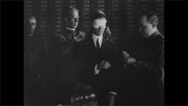 1910s: Intertitle card. Man places blindfold on other man. Man draws paper from bowl. Intertitle card. Photograph of soldiers.