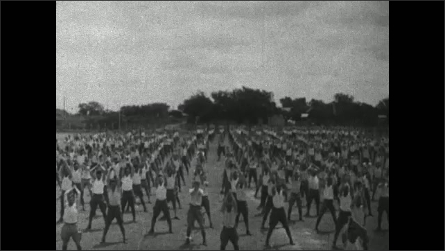 1910s: Soldiers march across field. Intertitle card. Soldiers exercise in field. Soldiers perform drills.