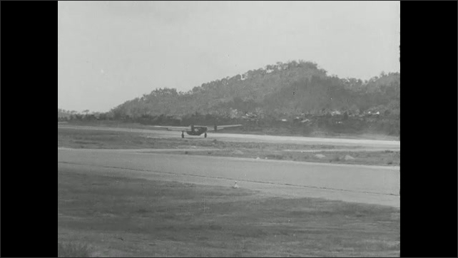 1940s: bomber landing on landing strip, soldiers running to help crew get out of bomber with damaged nose