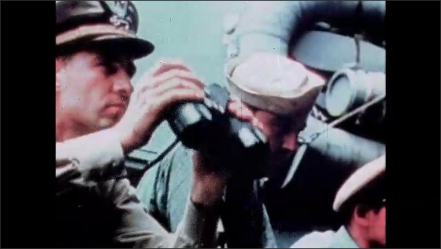 1940s: Depth charge sinks next to submarine underwater. Explosion on surface of sea. Officer on desk of battleship looks through binoculars. Submarine surfaces. Cannon on battleship fires. Soldier.