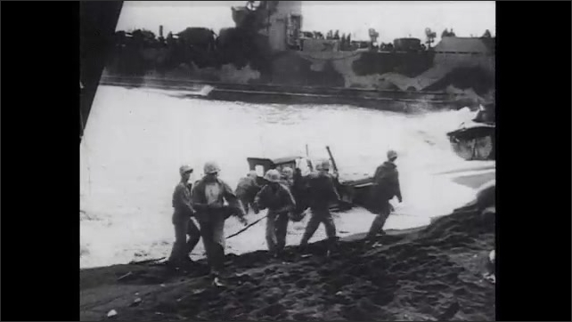 1940s: Military boat in water. Vehicles unload from landing craft boats on beach. Waves crash against destroyed vehicles on beach.