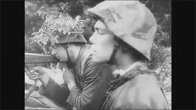 1940s: Soldiers walking through forest. Soldiers move through forest. Soldiers aim guns. Soldier looks through binoculars, points. Explosion. Destroyed tanks.