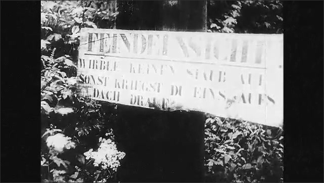 1940s: Soldiers ride bicycles. Road sign. Vehicles carry soldiers down road. Soldiers in camouflaged vehicle.
