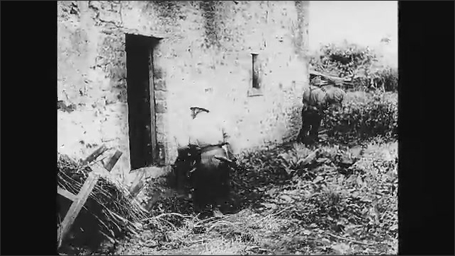 1940s: Soldier kneels in ditch, holds gun. Soldiers creep along roadside. Soldiers sits in ditch, aims gun. Tank rolls down road. Soldiers hide in ruins of town. Cannon fires.