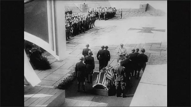1940s Germany: Nazi military funeral, soldiers lay down wreath of flowers. High angle of ceremony. Soldiers by coffin. Officer by coffin. Helmet on coffin. Officers saluting.