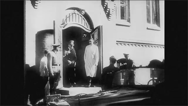 1940s Germany: Adolf Hitler talking to man in hospital bed. Hitler exiting hospital with officers. Crowd of people saluting. Hitler climbing into car. Women saluting.