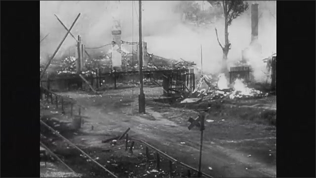 1940s Germany: Train driving on tracks. Train car destroying tracks. High angle, train yard on fire. Building on fire. People on tracks, explosions in background. Close up of man. Smoke over field.