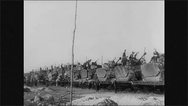 1940s Germany: Soldiers by train carrying tanks. Soldiers sitting on tanks on train cars. Shots of tanks driving. Soldier by truck. Close up of truck tires driving.