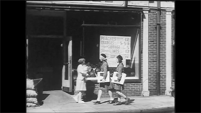 1940s: Children leave building. Man posts USO poster in shopfront window. Girls in uniform walk into store. Boy Scout walks down path. Woman posts The Visiting Nurse poster in shopfront window.
