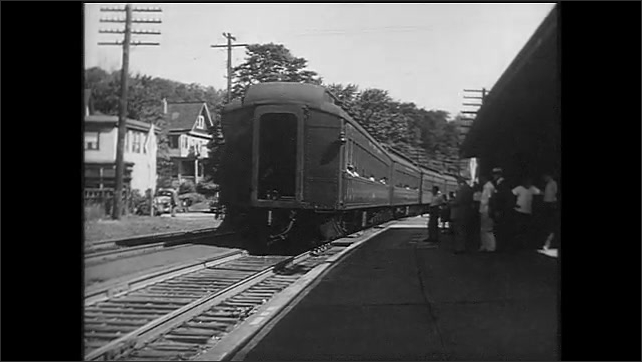 1940s: Woman smiles and waves. Soldier waves from steps of train. Conductor steps onto moving train. Woman stops smiling and touches her face and neck. Soldiers board ship.