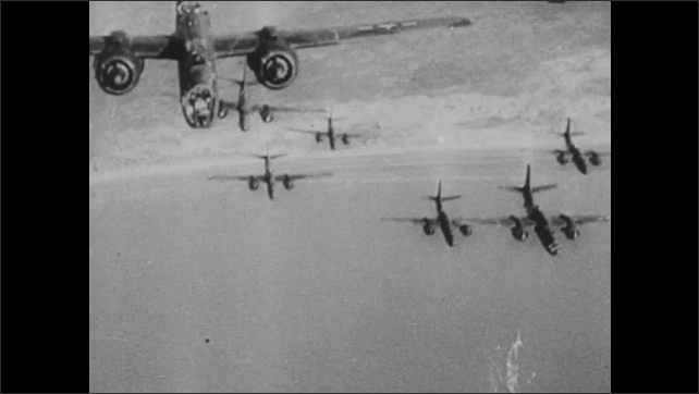 1940s: Nazi fortifications on beach. Planes fly in the sky. Bombs fall from planes. Pilot launches bombs.