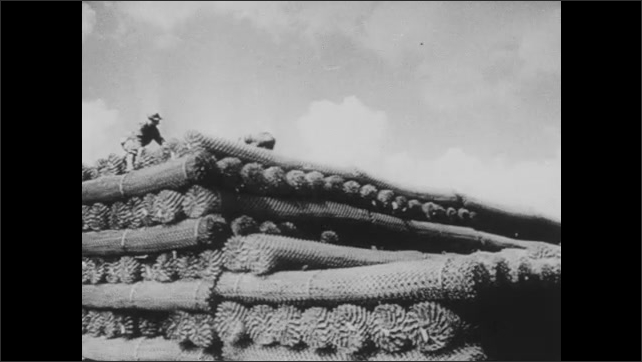 1940s: Soldiers unload cargo from ships. Stockyards full of tanks and weapons of war.