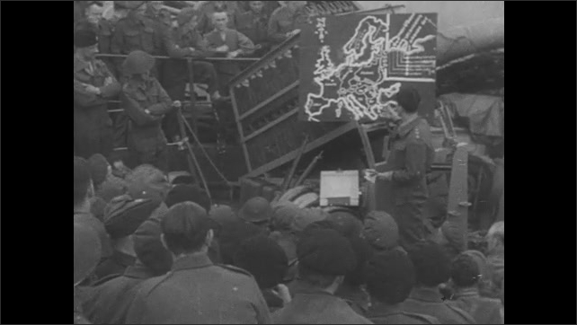 1940s: Soldiers wait on ship deck. Military officers give orders to soldiers.