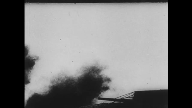 1940s: Men aim cannons, load chambers. Man orders fire. Cannons fire from beach towards ships at sea. Man looks through periscope.
