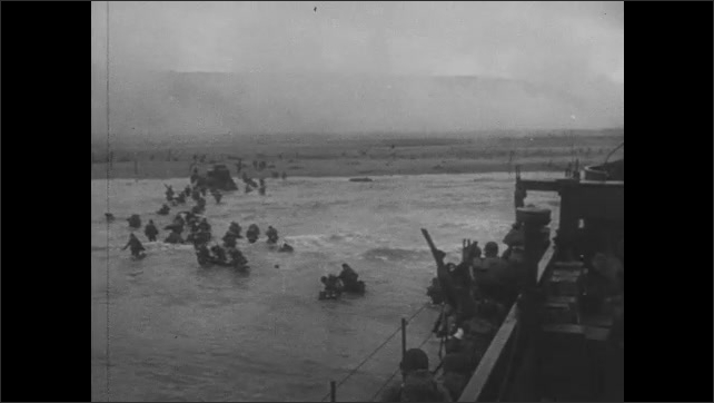 1940s: Transport ships land on beaches. Soldiers disembark from ships. Ship crashes against rocks.
