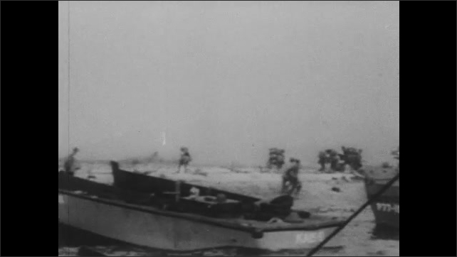 1940s: Boats and soldiers arrive at beach. Concrete blockade floats towards shore.