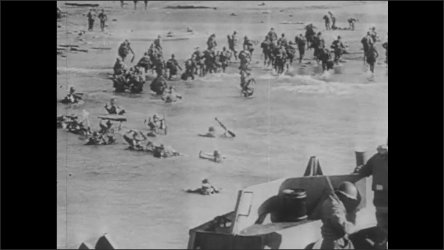 1940s: Soldiers camp by American flag on beach. Soldiers communicate via light flashes from beach. Soldiers disembark from ship. Soldiers tend to wounded men on beach.