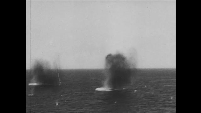 1940s: War ships fire cannons. Cannons on beach return fire. Explosions in water.