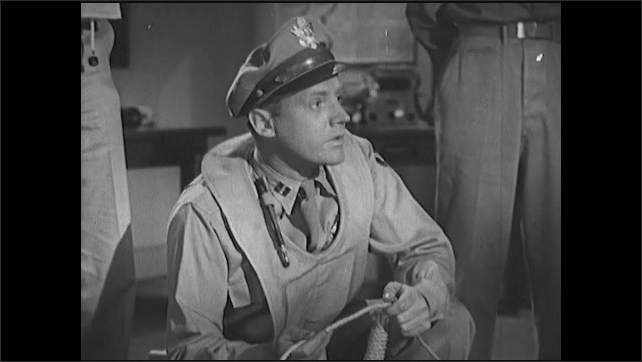 1940s: Officer crotches near life raft and speaks. Officer walks to table and demonstrates survival equipment. Officer instructs crew of airmen.