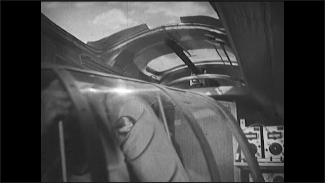 1940s: Officer speaks in cockpit of bomber plane. Soldier moves through body of plane and removes window. Tail gunner straps in. Officer speaks in cockpit.