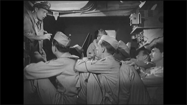 1940s: Officer speaks to airmen crew in communications room of bomber. Soldiers place their hands behind their heads and brace for impact.