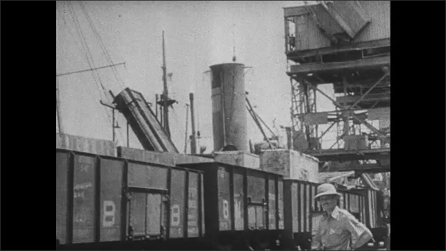 1940s: Flat of goods lowered to the ground. Men push train car. Men look at row of tanks. People carrying goods disembark from vessel.