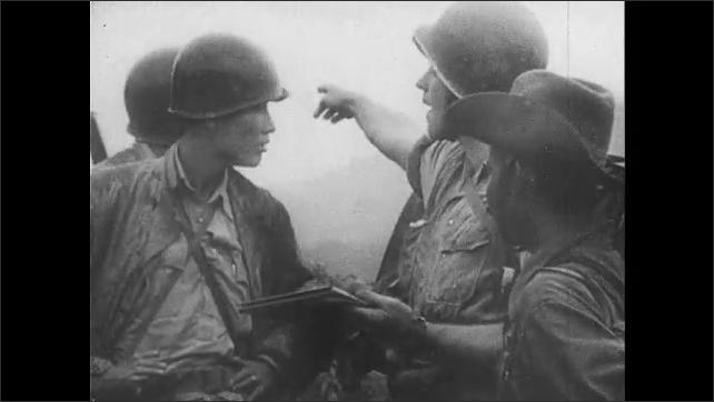1940s: Men build bridge. Soldiers huddle. Man points. Explosion. Men climb over hill.