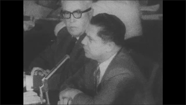 1960s: Jimmy Hoffa sits at table and talks into microphone as man next to him watches, listens, scratches his ear, whispers to Hoffa, Hoffa drinks from glass of water
