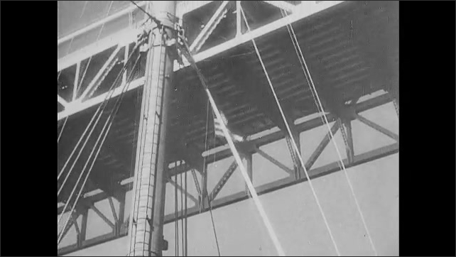 1940s: Large boat goes underneath bridge. Bridge. Boat at sea. Man looking through binoculars on boat. Sea.