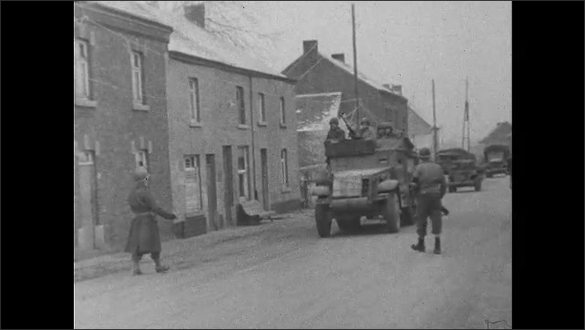 1940s: soldier inspecting a suspected spy's dog tags, truck drives into town and stops to talk to soldiers