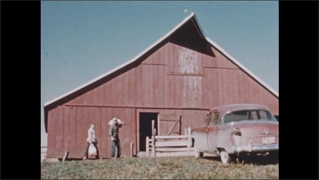 1950s: Exterior of schoolhouse. Car pulls up to barn and man gets out.