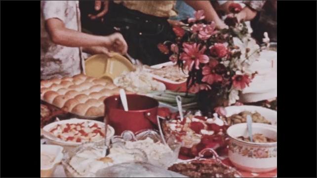 1950s: People dish up food at buffet.