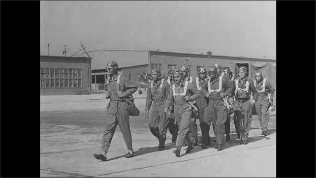 1940s: Soldiers walk around fighter planes parked on concrete runway. Group of pilots walk toward fighter planes on runway.