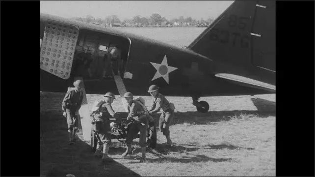 1940s: Airplanes.  Soldiers jump out of planes and run across field.  Men move weapon down ramp.