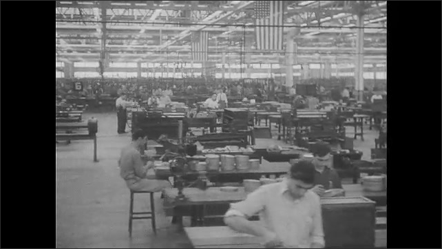1940s: Officers inspect plane construction plant. Men work at benches in factory. Military officers talk and inspect airplane factory.