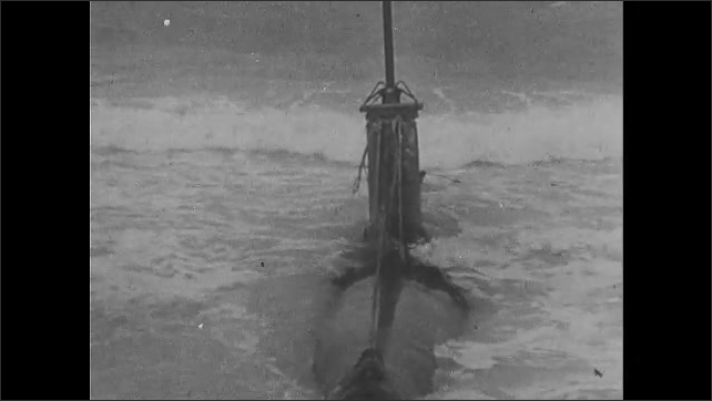1940s: Waves wash over Japanese submarine marooned on coast. Soldiers observe marooned submarine. Soldiers run from bunker and hide behind sandbags.