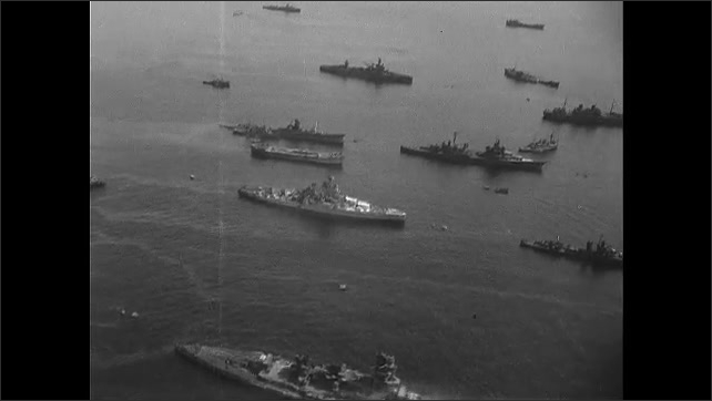 1940s: Aerial view of damaged ships on water.
