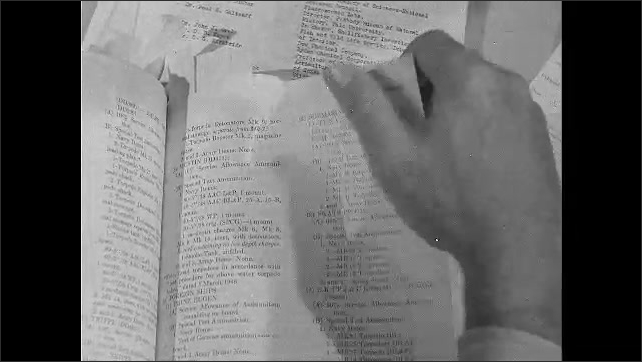 1940s: Close up of documents on table, hand turns pages of document.