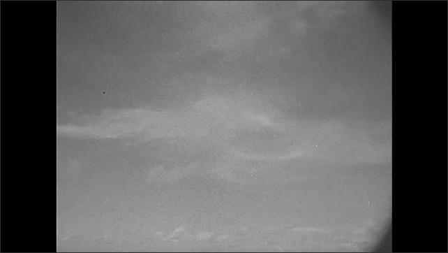 1940s: Clouds.  Ocean.  Man on boat uses machine to drop anchor.