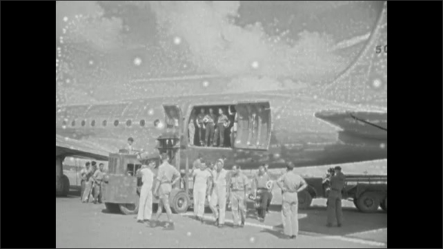 1940s: Army medic vehicles. Man holds up clapboard. People walk around airplane on tarmac. Army medic vehicle pulls up to airplane.